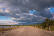 Rural road along the reservoir in the atmosphere before the rain is falling.