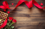 Hearts,chocolate truffles and red roses on wooden background