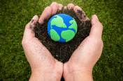 Soil  and earth simulation in hand on grass background, earth day concept
