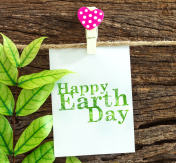 Happy Earth Day paper note hanging by red heart clips