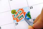 Woman fingers with pen writing reminder Earth Day in calendar.