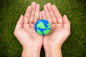 earth simulation in hand on grass background, earth day concept