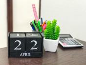 Black color wooden calendar on desk with fake small tree in pot , the date show of earthday April 22