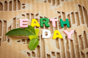 Earth Day wording on abstract brown torn cardboard background