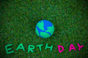 earth simulation and earth day word on grass background, earth day concept