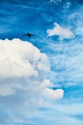 Airplane flying over beautiful fluffy clouds in vibrant blue sky