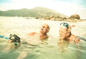 Senior couple vacationer having genuine fun on tropical Koh Lipe sea in Thailand - Snorkel tour in exotic scenario - Active elderly and travel concept around world - Warm desaturated greenery filter