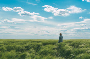 Farmer walking through green wheat field on windy spring day