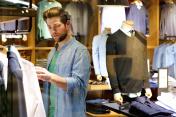 Young man looking at clothes to buy at shop