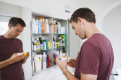 Man looking at bottles from medicine cabinet