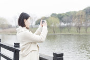 woman taking pictures by phone on footbridge