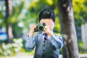 Little boy taking photos in the park