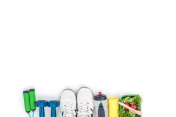 top view of dumbbells, skipping rope, sports shoes, bottle of water and vegetable salad isolated on white