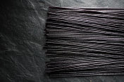 Black dry rice noodles on black stone free space