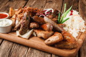 Baked sausages and meat on wooden board. Junk food
