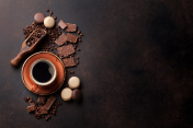 Coffee cup, chocolate and macaroons on old kitchen table