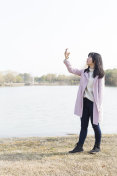woman taking pictures by smartphone at a spring afternoon