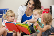 Hispanic female teacher reading a book to cute preschool students