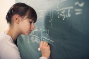 Little girl writing difficult mathematics equations