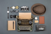 Journalist or private detective workplace - typewriter, camera, hat, recorder and other stuff