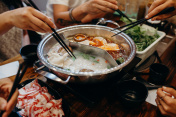 Korean hot pot meal. Hands taking food with chopsticks.