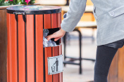 side view of man hand throw rubbish into dustbin