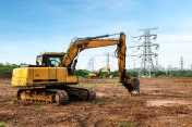 The excavator is on the construction site, far away from electric piles and substations.