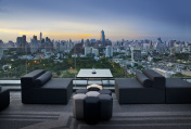 Sofa on terrace overlooking green park and building, Bangkok, Thailand