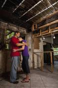 Sad couple hugging inside house with fire damage