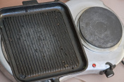 Closeup of a electric hot plate and black ribbed pot