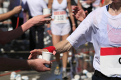 Running athletes grabbing water