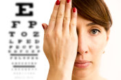 Young woman is covering his face with hand and checking his vision. Chart for eye sight testing in background.