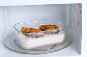 Container with food in the microwave. Rice and fish