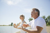 Middle-aged couple performing tai chi on beach