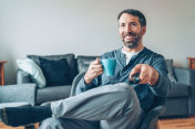 Smiling man sitting comfortably and watching TV