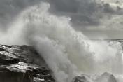 Stormy wave crashing over rocky coast