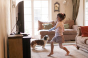 Little girl dancing in front of the TV at home