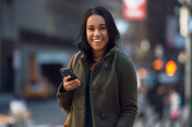 Beautiful young happy latin woman texting on mobile phone