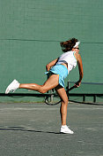 female senior tennis player swinging a racquet