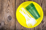 Plastic disposable tableware on wooden table