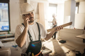 Manual worker talking on mobile phone at construction site.