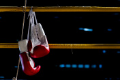 boxing gloves hangs off the boxing ring