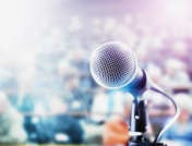 Brightly lit microphone in front of out-of-focus audience