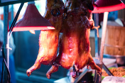 Chinese streetfood: Roasted piglets hanging on display on market