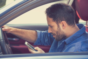 man using texting on mobile phone while driving a car