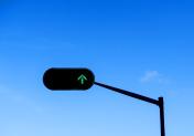 Green Arrow Traffic Light Against a Blue Cloudy Sky