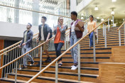 Group of students descending wooden stairs in modern college interior