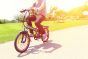 A man riding on a electric bicycle in a park