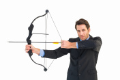 Serious businessman practicing archery looking at camera