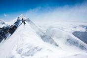 Climbers balancing in blizzard on a narrow mountain ridge